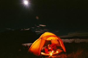 man-reading-in-tent-at-night-with-cerro-gordon-wiltsie